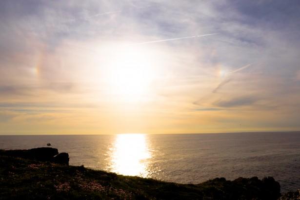 Ceci est une photo du soleil au dessus de la mer pris de la terre.